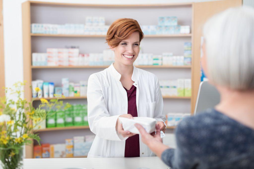 Ältere Dame kauft Medikamente in einer Apotheke.